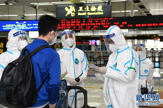 在深圳湾口岸入境大厅,海关工作人员核对入境旅客的健康申明卡(4月3日摄)。 新华社记者 梁旭 摄