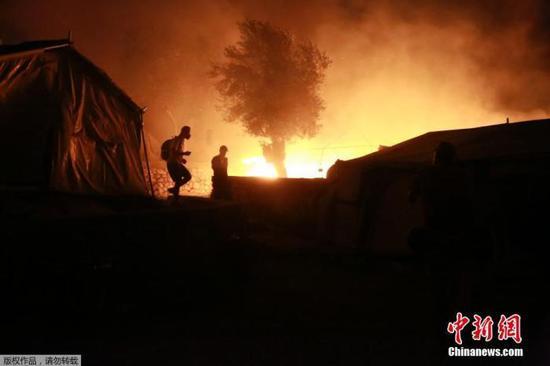 当地时间9月9日,希腊莱斯博斯岛的莫里亚难民营发生大火后,难民脱离着火地。