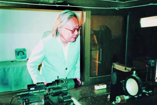 """1993年,洪晶在观察""""激光焊点检测仪""""。"""
