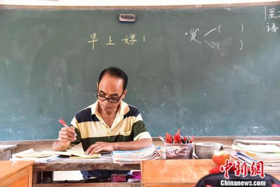 周宏军早上到教室后先批改作业。