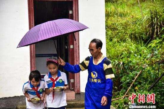下雨时,周宏军为学生撑起伞。