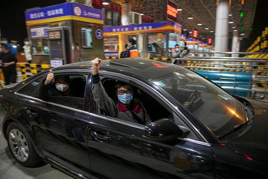 """4月8日零点,武汉正式消弭离汉通道管控,第一辆幼客车驶出""""武汉西""""高速路口。澎湃消息记者 孙湛 图"""