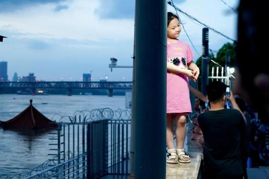 7月13日,湖北武汉市,市民在即将被吞没的武昌黄花矶凉亭前拍照。图/人民视觉