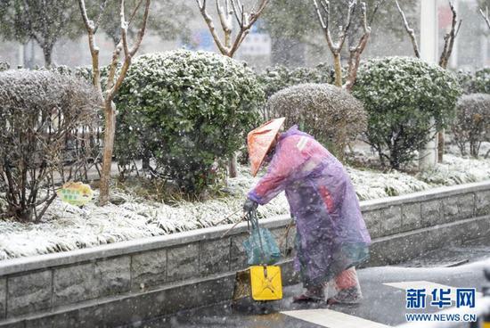 在武汉市汉口火车站,一名环卫工人在雪中工作(2月15日摄)。 新华社记者 才扬 摄