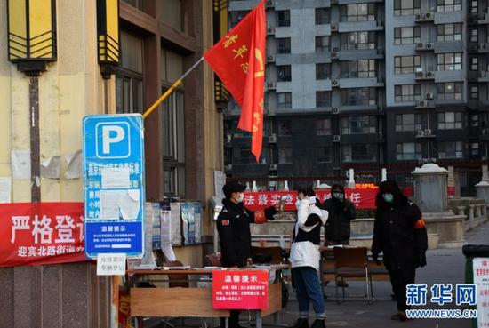 在河北省三河市燕京航城社区门口,居民在接受体温检测(2月23日摄)。 新华社发