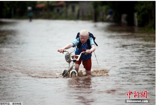 """资料图:当地时间2020年11月18日,洪都拉斯马可维亚,飓风""""约塔""""过境后,一名儿童推着自行车经过洪水泛滥的道路。"""