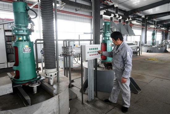 资料图:技术工人在操控沉淀杂质的沉钒逆答釜设备。 (新华社)