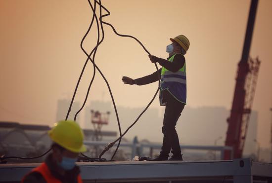 2月3日,工人在武汉雷神山医院建设工地施工。疫情期间,武汉市新建了火神山、雷神山医院,改造建成方舱医院33个,提供方舱医院床位35673个。摄影/长江日报 陈亮