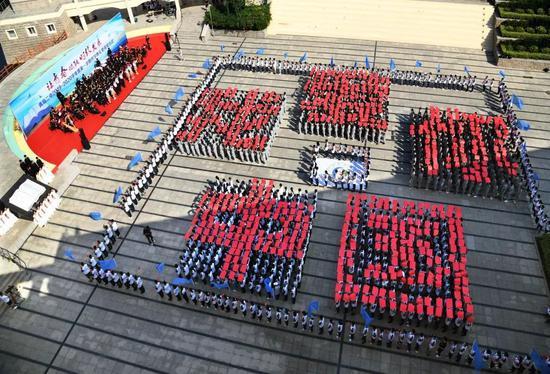 """2019年9月1日,青岛二中学生在开学典礼上摆出""""我爱你中国""""字样。图片来源:新华社"""