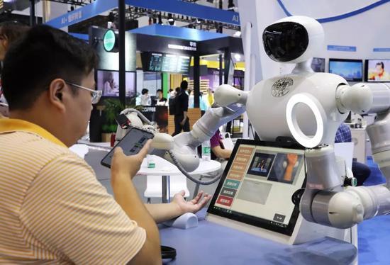 """▲在2019世界人工智能大会上,一名参观者拍摄一款自主交互中医四诊机器人的""""看病""""过程。(新华社)"""