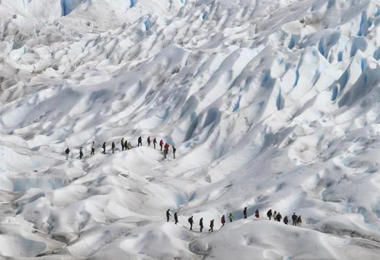 卡拉法特附近的莫雷诺冰川边缘徒步的游客