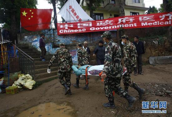 2015年4月28日,在尼泊尔首都加德满都以北30公里的杜里凯尔镇,尼泊尔士兵运送一名伤者到中国政府医疗队接受救治。尼泊尔25日中部地区发生8.1级强烈地震,中国政府医疗队27日早抵达尼首都加德满都后立即为灾民提供医疗救援。 新华社发(普拉塔普·塔帕摄)