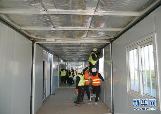 1月18日,在河北省石家庄市黄庄公寓隔离场所项目工地,工人在安装集成房屋。新华社记者 杨世尧 摄