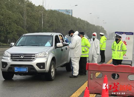 黄冈各大十字路口均有卡口,执勤人员检查过往车辆。