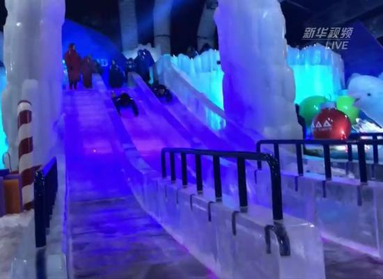 游客趴着滑下冰滑梯。