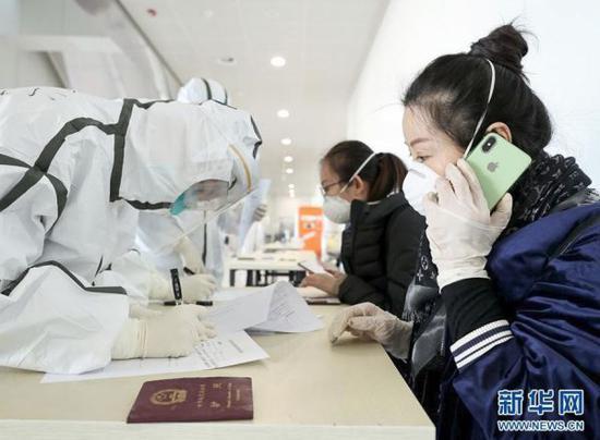 3月7日,海关关员在北京首都国际机场T2航站楼对乘客进行前置医学排查。(新华社记者 陈建力 摄)