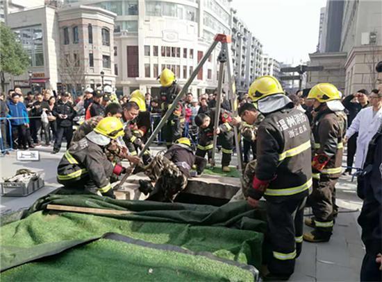 消防人员下井声援。温州都市报 图