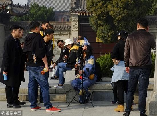 ▲2018年3月,西安一幼伙街头扮济公玩直播,吸引多多游客围不都雅。图/视觉中国