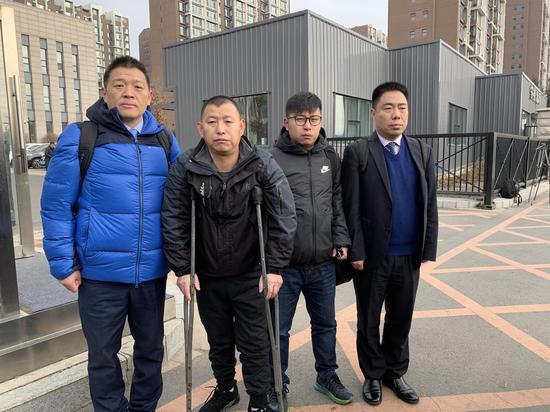 今天上午,金哲宏(左二)在代理律师和儿子的陪伴下走出法庭。新京报记者王巍摄