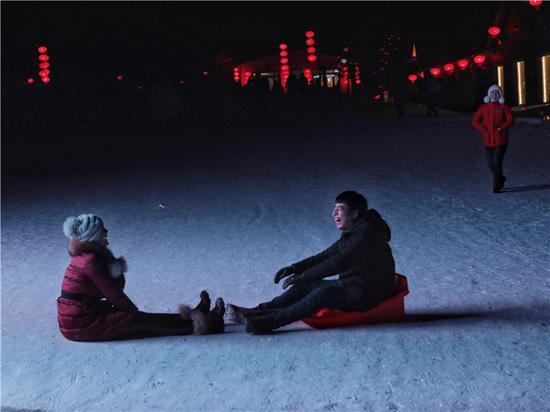 雪乡景区内,游客在玩拉雪橇。景区大屏幕投射出的光线照亮了他们,大屏幕上逆复播放着投诉电话以及关于明码标价、不准宰客的通告。新京报记者 王嘉宁 摄影报道