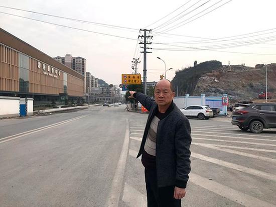 """12月13日,田茂平站在国道209上,这条凤凰县的""""城北大道""""当年有他""""扩建拉直"""",因为一份文件,他的命运发生逆转。澎湃新闻记者谭君 图"""