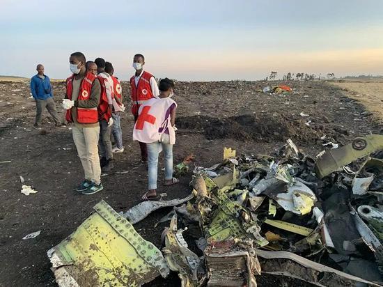 3月10日,在亚的斯亚贝巴附近,救援人员在坠机现场清理飞机残骸。(新华社记者王守宝摄)