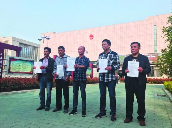 """2018 年 4 月 11 日下午,""""五周杀人案""""的 5 名被告人被宣告无罪。他们拿着无罪判决在安徽高院前合影。 新京报记者 曹林华 摄"""