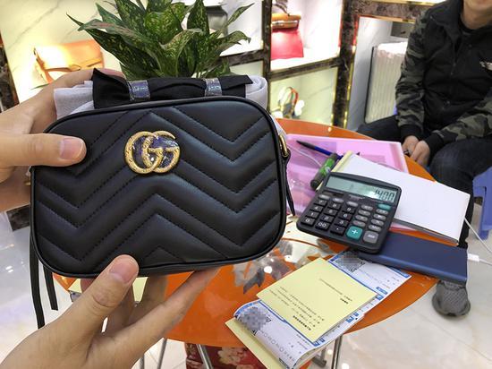 3月15日上午,广州市白云世界皮具贸易中心旁桂花岗小区。售假窝点的老板把一款奢侈品手包的价格打在计算器上,让记者选购。 新京报记者 吴江 摄