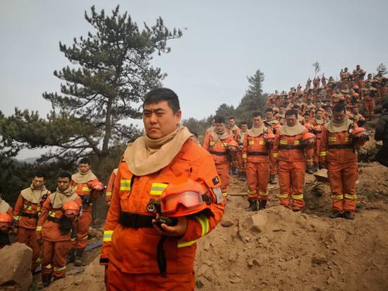 沁源火灾执行任务的消防员集体面向西,送别凉山战友。消防供图