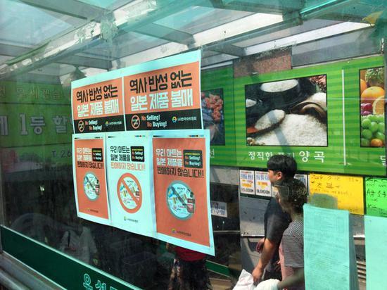 """韩国超市入口贴着告示,上面写着""""停止贩卖不反省历史的日本的商品""""(朝日新闻)"""