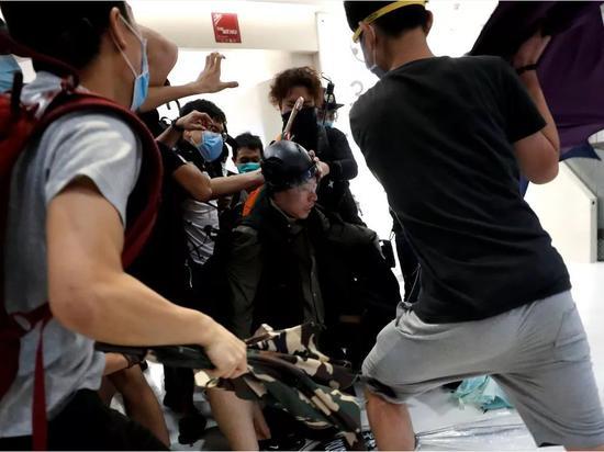 多名暴徒用雨伞等围殴一名警察。