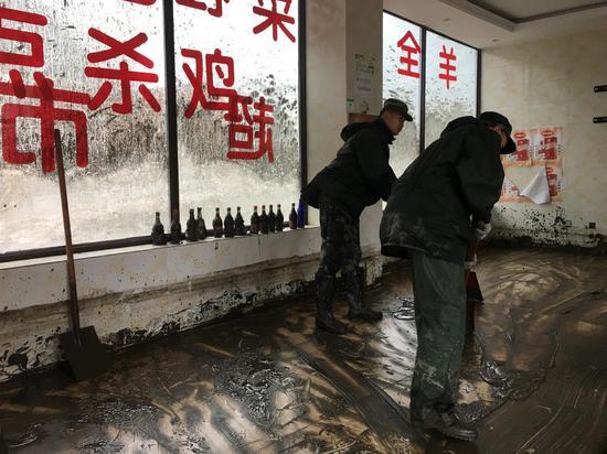 8月22日,两位武警在帮助清理村民所经营饭店中的淤泥。 新京报记者 周世玲 摄