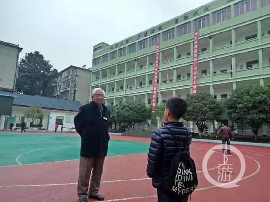 2018年12月5日,湖北赤壁正扬小学内75岁的校长吴震球在和学生对话。