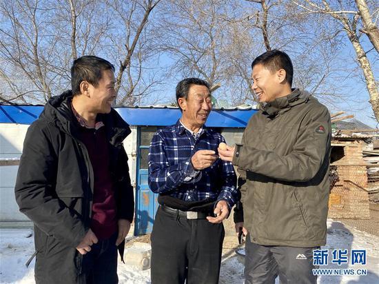 黑龙江省大庆市杜尔伯特蒙古族自治县一心乡前进村驻村工作队队长、第一书记慕海军(右)、工作队队员韩明祥(左)和69岁的脱贫户杨双交流(2020年1月4日摄)。新华社记者 杨思琪 摄