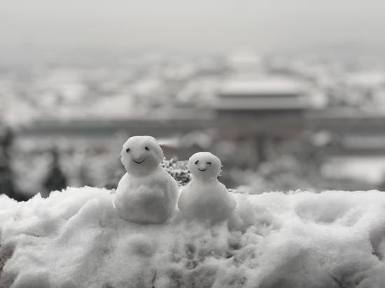 前来登高赏雪的游客堆首了雪人。景山公园 供图
