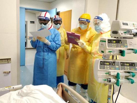 △2月11日,在武汉同济医院中法新城院区ICU病房内,来自北京协和医院的医护人员在病床旁查房交班。