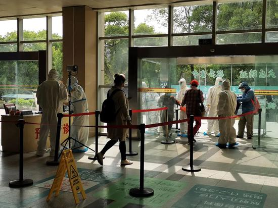 ▲4月6日,进入医院前,求诊者必要登记小我信息并测量体温。新京报记者王双兴摄