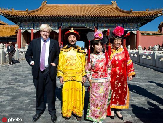 2013年10月15日,时任伦敦市长的鲍里斯·约翰逊访问中国第三天,参观紫禁城,并与穿着清朝皇室服装的游客合影留念/IC Photo