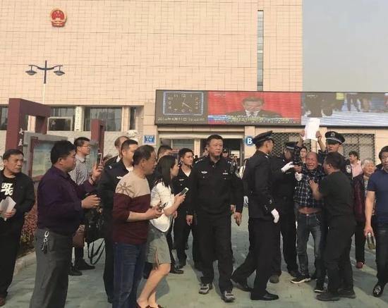 """""""五周""""被宣告无罪后,一名被告人高高举起了无罪判决。新京报记者 曹林华 摄"""