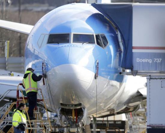 这是3月13日,在美国华盛顿州伦顿市的波音工厂,工人站在一架波音737-8客机前。 新华社/美联