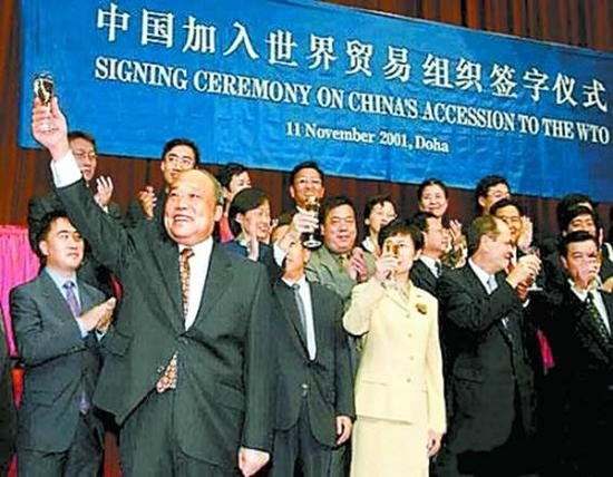 2001年11月11日,�r任外��Q部部�L石�V生在卡塔��首都多哈�e行的中��加入世�Q�M��h定���字�x式上�e杯�c�R。(新�A社�l)