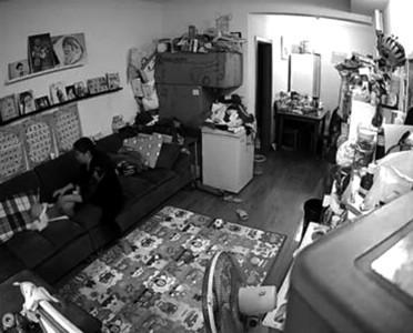监控?#24736;?#26174;示,育婴嫂赵女士在客厅中抓起孩子在半空中用力摇甩,还多次?#39057;?#22352;在沙发上的婴儿。截屏图