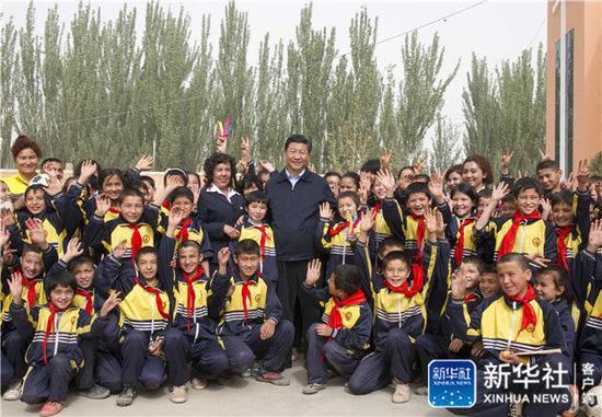 2014年4月28日,習近平在新疆疏附縣托克扎克鎮中心小學同師生們合影。新華社記者 謝環馳 攝