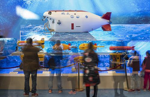 """11月18日,观众在观看""""蛟龙""""号载人潜水器等模型(慢门拍摄)。新华社记者 才扬 摄"""