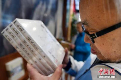 资料图:读者拿着金庸先生所著作品。中新社记者 韦亮 摄