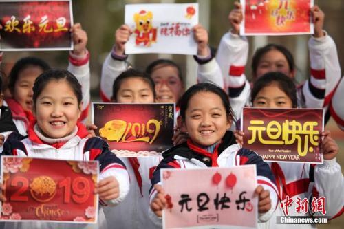 """2018年12月29日,江蘇揚州,小學生們手持""""喜迎元旦""""的祝福語,喜迎新年的到來。孟德龍 攝"""