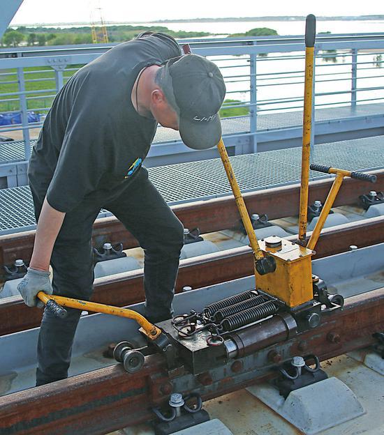 中铁大桥局中俄同江铁路大桥项目的建设者正在对钢轨精度进行微调(6月4日摄)。本报记者谢锐佳摄
