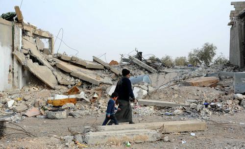 原料图片:2017年12月23日,在叙利亚拉卡省西南的迪卜斯阿夫南村,村民走过损毁的房屋。新华社发