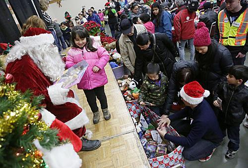"""""""圣诞老人""""现身添拿大温哥华劳工圣诞大餐现场,向儿童施舍圣诞礼物。(新华社发)"""