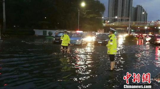 图为兰州交警在雨中疏导,确保道路安全。 钟欣 摄
